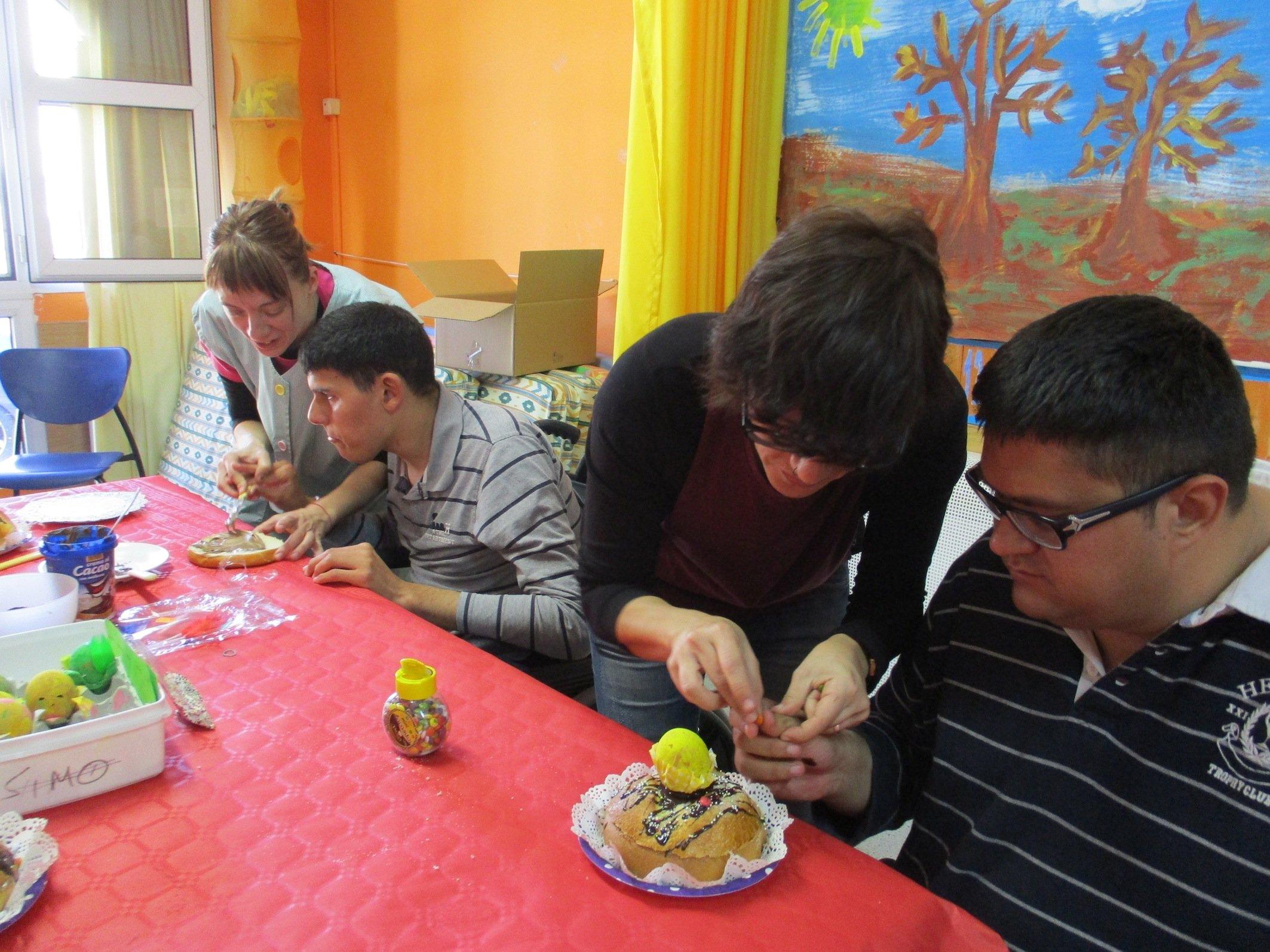 Usuaris del CAE l'Àngel preparant mones de pasqüa